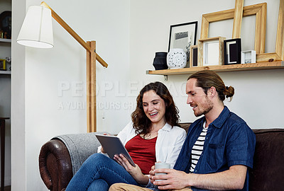 Buy stock photo Shot of an affectionate young couple using a tablet while sitting on their sofa at home