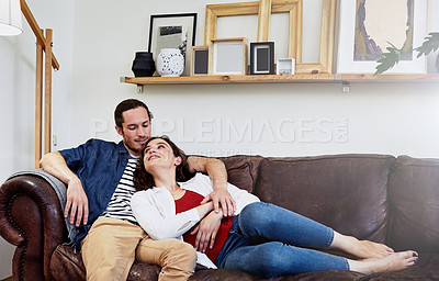 Buy stock photo Shot of an affectionate young couple relaxing on their sofa at home