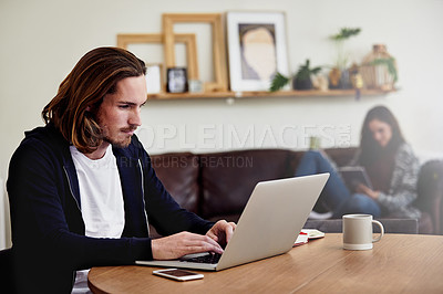 Buy stock photo Shot of a handsome young man working at home with his wife in the background