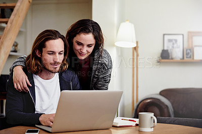 Buy stock photo Shot of an attractive young woman watching her husband as he works from home