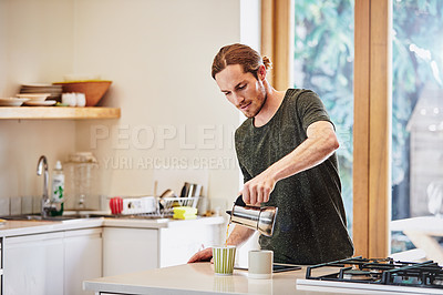 Buy stock photo Shot of a handsome young man preparing coffee in the kitchen at home