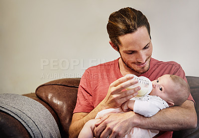 Buy stock photo Shot of a handsome young man feeding his newborn baby girl on the sofa at home