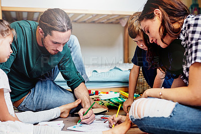 Buy stock photo Shot of a young family of four drawing while sitting on the floor of a child's bedroom