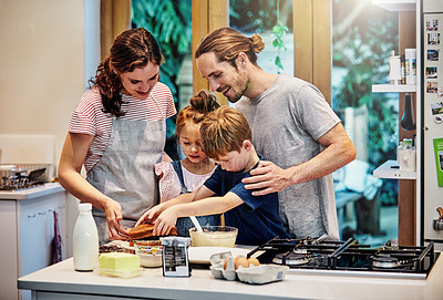 Buy stock photo Shot of a happy young family of four baking in the kitchen at home