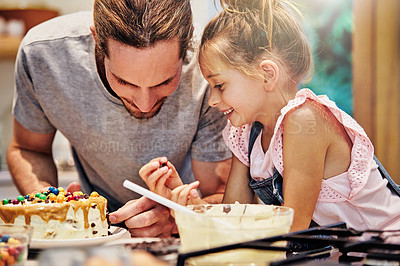 Buy stock photo Shot of a handsome young man baking a cake with his daughter
