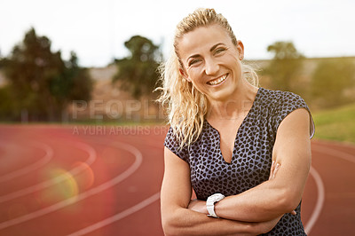 Buy stock photo Portrait of an athletic young woman standing on the track with her arms folded