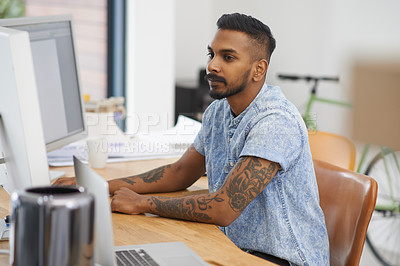 Buy stock photo Shot of a young designer working on a computer in an office