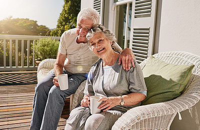 Buy stock photo Shot of a happy senior couple enjoying their morning coffee on the patio at home