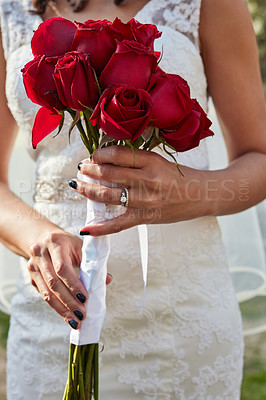 Buy stock photo Cropped shot of an unrecognisable bride holding a bouquet of red roses on her wedding day