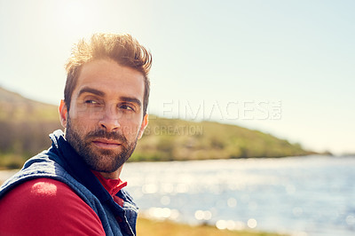 Buy stock photo Shot of a thoughtful hiker admiring the view of a lake on a sunny day