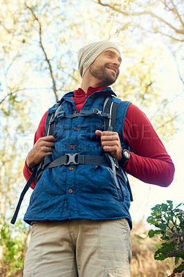 Buy stock photo Shot of a happy hiker out on a mountain hiking trail on his own