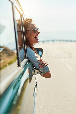 Buy stock photo Cropped shot of an attractive woman hanging out of a car window while enjoying a roadtrip