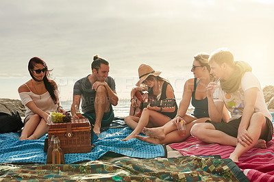 Buy stock photo Shot of a group of happy young friends enjoying a picnic on the beach together