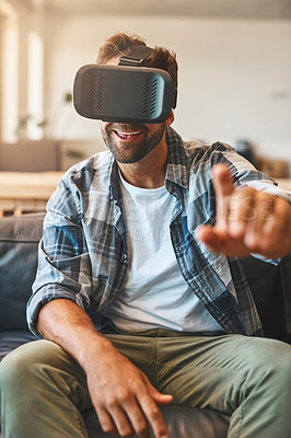 Buy stock photo Shot of a young man using a virtual reality headset on the sofa at home