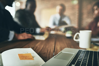 Buy stock photo Shot of a laptop and paperwork on a boardroom table with unidentifiable businesspeople meeting in the background
