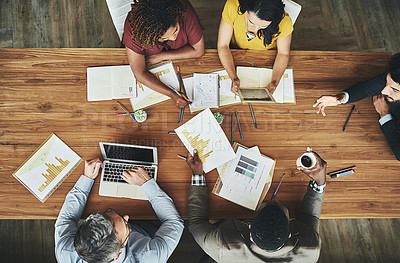 Buy stock photo High angle shot of a team of businesspeople meeting around the boardroom table in the office