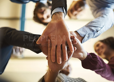 Buy stock photo Low angle shot of a team of businesspeople piling their hands on top of each other in the office