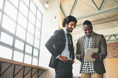 Buy stock photo Shot of two well-dressed businessmen brainstorming together over a tablet in their office