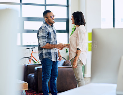 Buy stock photo Shot of a young man and woman shaking hands in a modern office