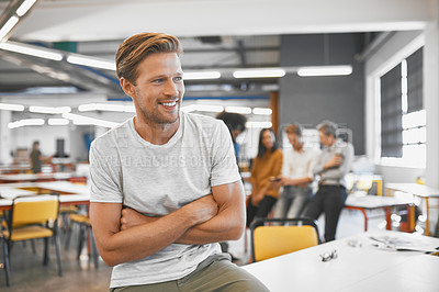 Buy stock photo Cropped shot of a handsome young businessman in the office with his colleagues in the background