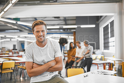Buy stock photo Cropped portrait of a handsome young businessman in the office with his colleagues in the background