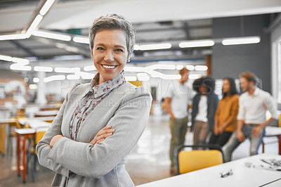 Buy stock photo Cropped portrait of an attractive mature businesswoman in the office with his colleagues in the background