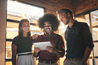Buy stock photo Shot of a group of designers working together on a digital tablet