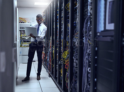 Buy stock photo Cropped shot of a IT technician working on his laptop while standing inside of a server room