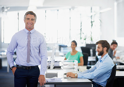Buy stock photo Portrait of a handsome mature businessman standing in an office with his employees in the background