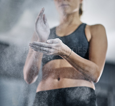 Buy stock photo Shot of a female athlete coating her hands with sports chalk