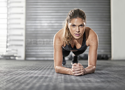 Buy stock photo Shot of a young woman doing a plank exercise at the gym