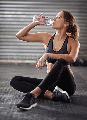 Buy stock photo Cropped shot of a young woman drinking from her water bottle at the gym