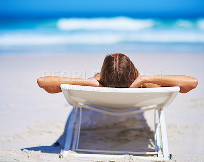 Buy stock photo Rearview shot of a young woman relaxing on the beach
