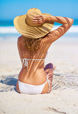 Buy stock photo Rearview shot of a young woman sitting on the beach