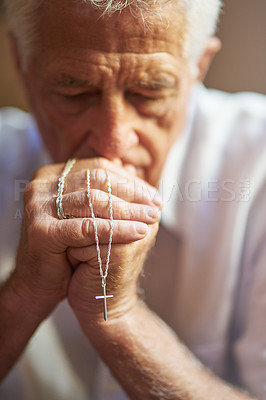 Buy stock photo Cropped shot of a senior man holding a rosary while praying for a miracle