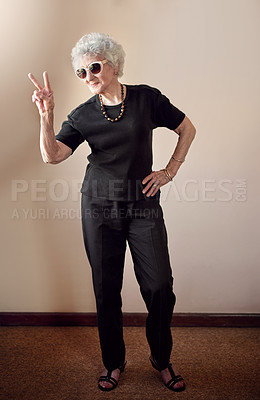 Buy stock photo Shot of a cool senior woman wearing sunglasses and showing a peace gesture