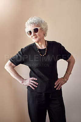 Buy stock photo Shot of a cool senior woman wearing sunglasses and posing with attitude