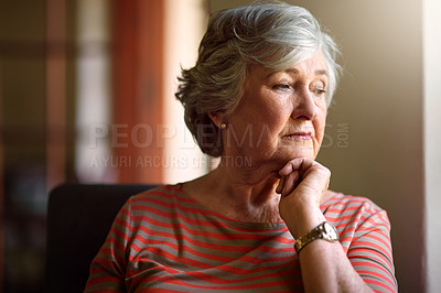 Buy stock photo Shot of a thoughtful senior woman looking out of the window at home