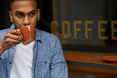 Buy stock photo Shot of a handsome young man enjoying a cup of coffee at a cafe