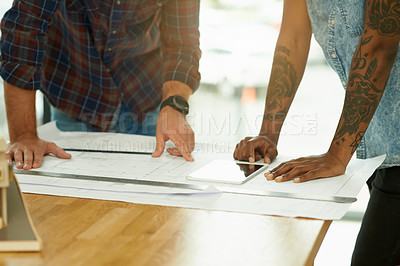 Buy stock photo Shot of two unidentifiable architects working on blueprints in an office