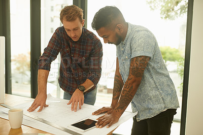Buy stock photo Shot of two young architects working on blueprints in an office