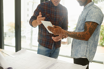 Buy stock photo Shot of two unrecognisable architects working together on a digital tablet in an office