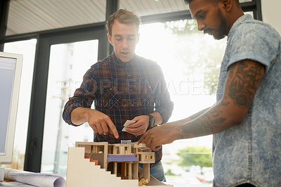 Buy stock photo Shot of two young architects working together on a building model in an office