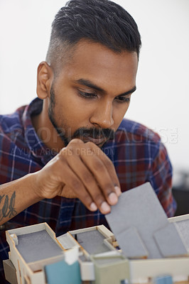 Buy stock photo Shot of a focussed young architect constructing a model of his building design in the office