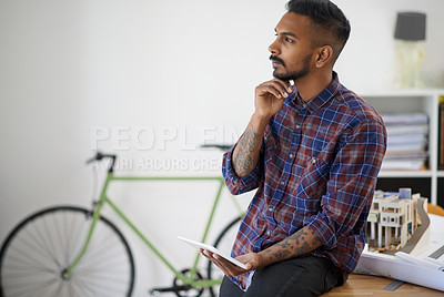 Buy stock photo Shot of a creative young designer using his tablet while leaning on his desk in the office