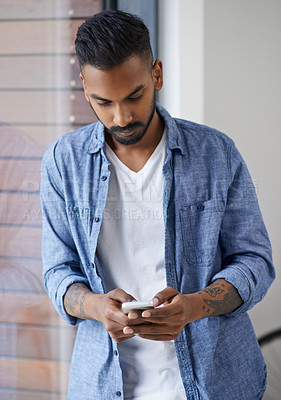 Buy stock photo Shot of a handsome young man texting on his cellphone