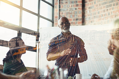 Buy stock photo Cropped shot of a mature businessman giving a presentation in the boardroom superimposed over railway tracks