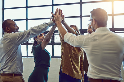 Buy stock photo Shot of a group of colleagues giving each other a high five in a modern office