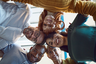 Buy stock photo Low angle shot of a group of colleagues huddled together in solidarity at work