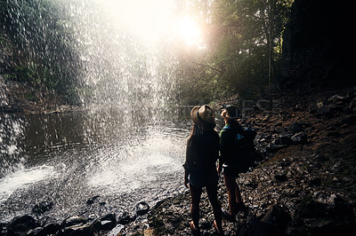 Buy stock photo Shot of two young women standing underneath a waterfall enjoying a day in nature